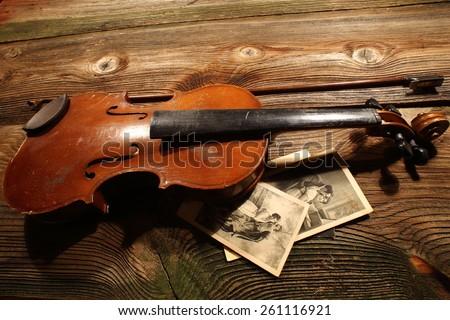 old broken violin on a wooden background/Old broken violin close up  - stock photo
