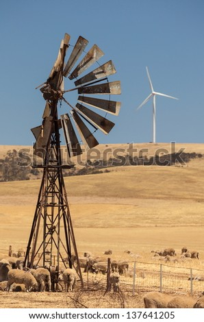 Old broken wind pump and new wind generators distorted by hot air. South Australia.