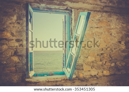 Old broken window with view of Aegean Sea - stock photo