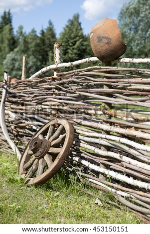 old broken wooden carriage wheel on wattled fence and pot background - stock photo