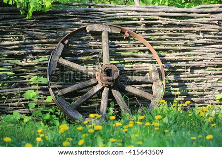 old broken wooden carriage wheel on wattled fence background - stock photo