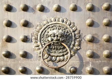 Old bronze lion door knocker on the door - stock photo