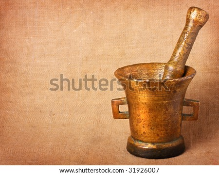 Old bronze mortar and pestle on sacking background - stock photo