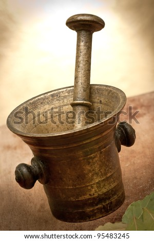 Old bronze mortar and pestle with bay leaves on yellow background - stock photo