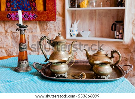 Old bronze tea set and a candlestick stand on the kitchen table in an old stone house