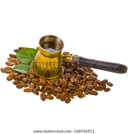 Old  bronze with wooden handle coffee maker and roasted coffee beans scattered decorated with green leaves, isolated on white background - stock photo