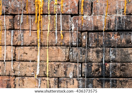 Old brown brick wall with candle drippings