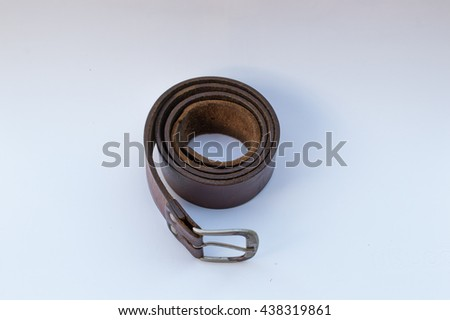 Old brown leather belt with buckle isolated on white background - stock photo