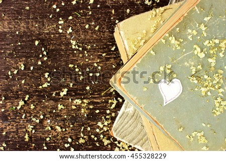 Old brown wooden background with dry petals of white flowers, stack of vintage books with shabby covers and and little paper heart. Copy space - stock photo