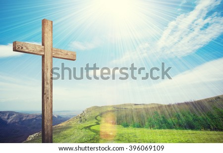 Old brown wooden cross, with sun flash on clouds background - stock photo