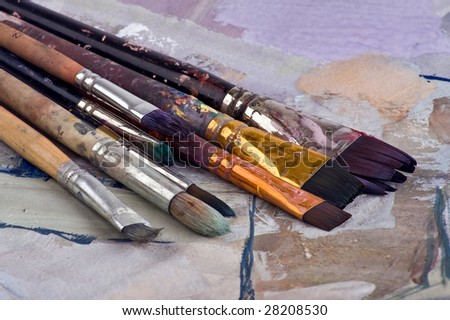 Old brushes over the paper with painting (palette) - stock photo