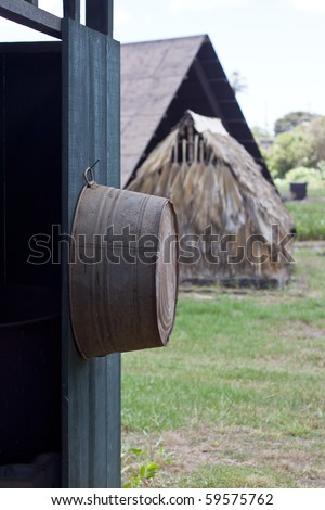 Old bucket hanging on wall - stock photo