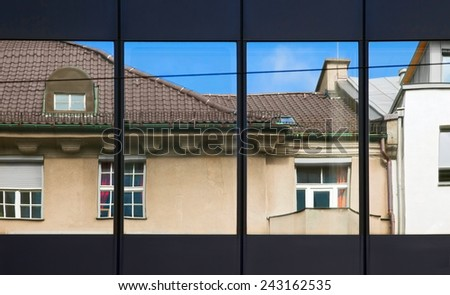 Old building architecture reflected in modern building. Front view of the building. Munich, Germany. - stock photo