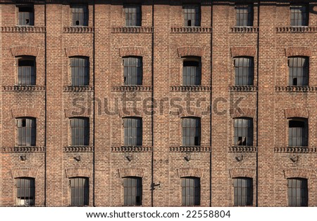 Old building built from bricks with many symmetrical windows - stock photo