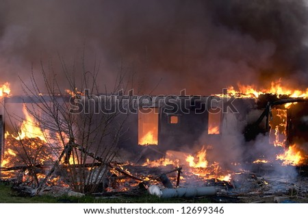 Old building engulfed in flames.  Fire departments involved in practice burn or controlled burn. - stock photo