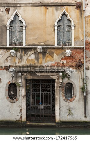 Old building facade with the entrance and sculptural faces in Venice, Italy. - stock photo