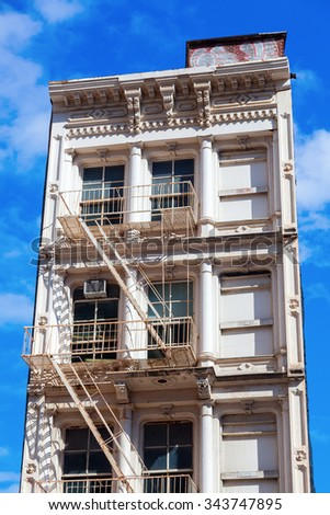old building in downtown Manhattan, NYC, with typical fire escape stairs  - stock photo