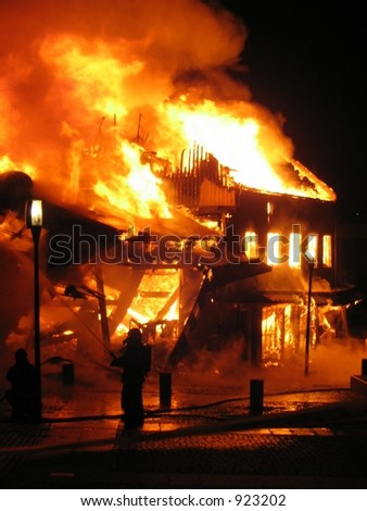 Old building in full flaming inferno, and a firefighter fighting the flames