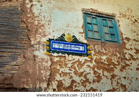Old building with run down facade with window and street sign, Cusco, Peru