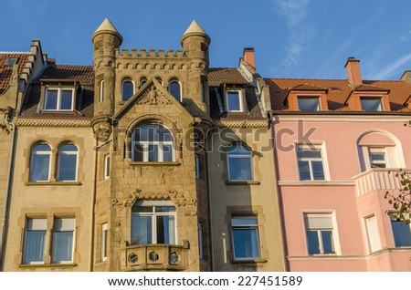 Old building with spires next to more modern houses - stock photo
