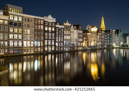Old Buildings along the Damrak in Amsterdam at night. Reflections can be seen in the water. - stock photo