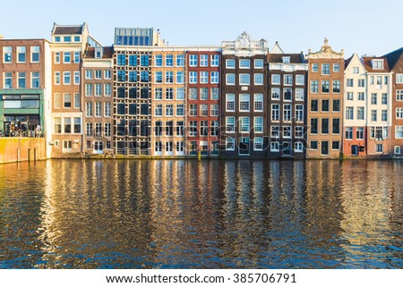Old Buildings along the Damrak in Amsterdam during the day. Reflections can be seen in the water. - stock photo