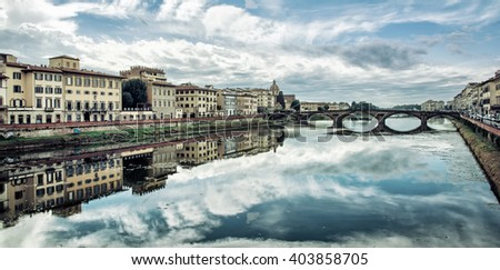 Old buildings and beautiful Ponte Santa Trinita mirrored in the river Arno, Florence, Tuscany, Italy. Dramatic cloudy sky. Travel destination. - stock photo