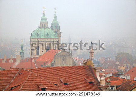 Old buildings and Saint Nicholas Church (Cathedral) in foggy afternoon, Prague, Czech Republic - stock photo