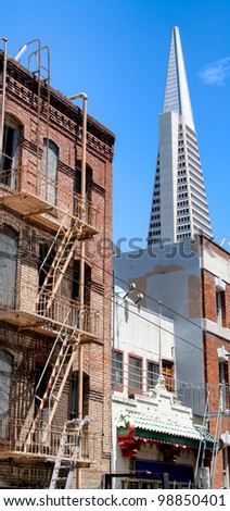 old buildings and tall scraper building on background