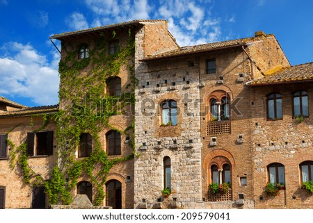 Old Buildings on the Cisterna square on blue sky, San Gimignano medieval town (UNESCO heritage), Siena, Tuscany, Italy