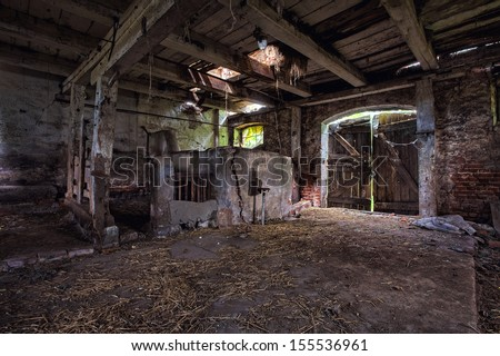 Old, built of wood and brick, abandoned barn. - stock photo