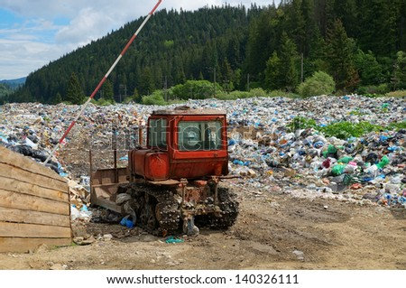Old bulldozer at working landfill site (nature pollution in Carpathian mountains, Ukraine) - stock photo