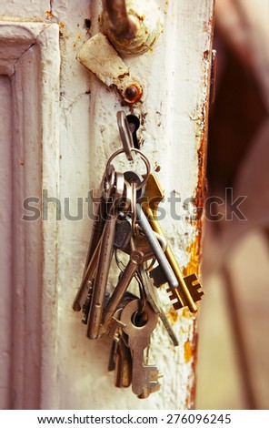old bunch of keys in the keyhole - stock photo