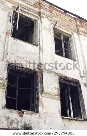 Old burnt house with charred wooden windows, bottom view - stock photo