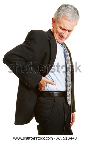 Old business man having back pain and holding hand to his aching back - stock photo