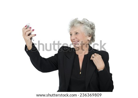 Old business woman holding mobile phone against a white background