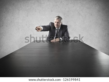 Old businessman at the head of a long black table indicates someone with aggression - stock photo