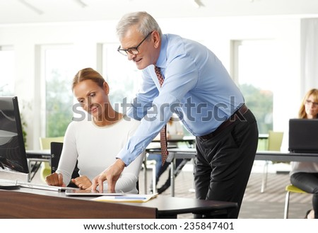Old businessman helping solution problem to business woman while sitting at office in front of laptop. Teamwork.