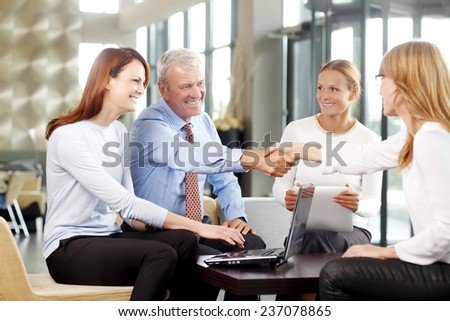 Old businessman shaking hands with confident business woman at meeting. - stock photo