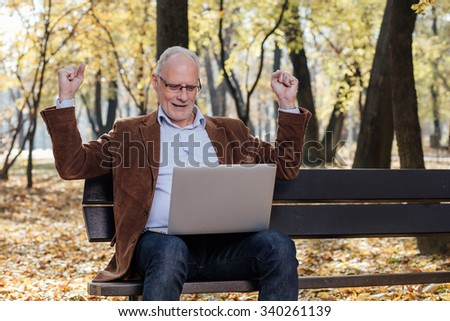 old businessmen sitting outside on a bench and working at laptop, very happy