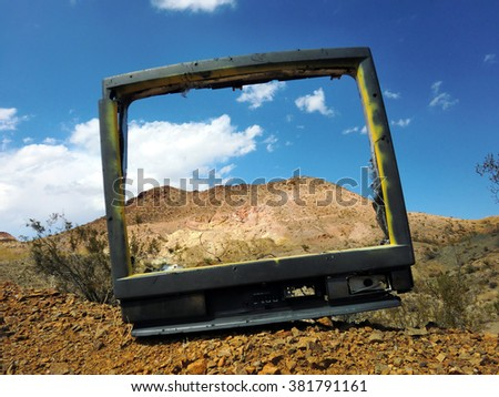 Old busted television shell framing desert mountain - landscape color photo - stock photo