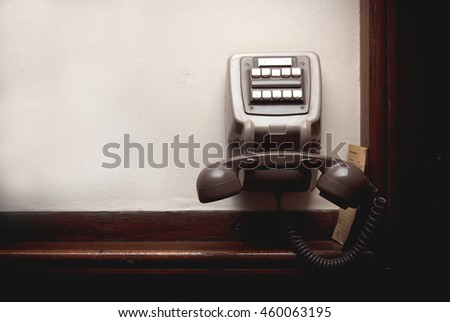 Old-button phone on a white wall. Tinted photo. Empty place. Blank space - stock photo