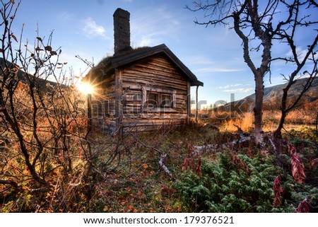 old cabin in the wilderness of sweden in autumn at sunrise - stock photo