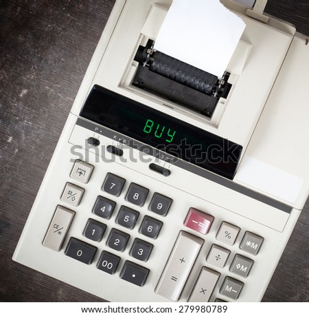 Old calculator showing a text on display - buy - stock photo