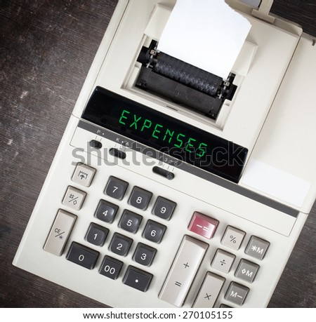 Old calculator showing a text on display - expenses - stock photo