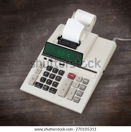 Old calculator with digital display showing a percentage - 50 percent - stock photo