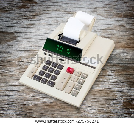 Old calculator with digital display showing a percentage - 70 percent - stock photo