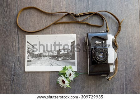 old camera and a black and white photo on a wooden table - stock photo