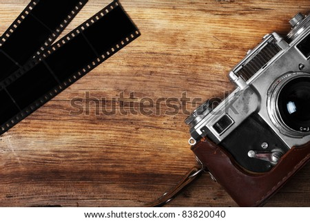 old camera and blank film strip on wooden table - stock photo