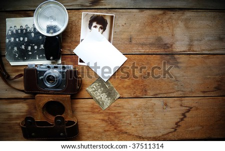 Old camera and  cards on wooden surface. Wooden background.